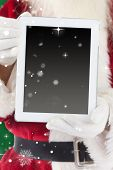 Santa claus showing tablet pc against green