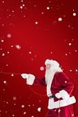Santa pulls something with a rope against red snowflake background