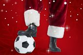 Santa Claus is playing soccer against red snowflake background