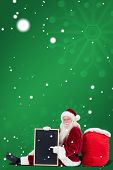Santa sits leaned on his bag with a board against green snowflake background