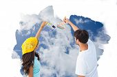 Happy young couple painting together against bright blue sky with clouds