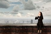 Young emotional businesswoman sitting on building top