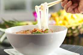 stock photo of crispy rice  - Closeup of a person eating Thai style crispy pork rice noodle soup from a bowl with chopsticks - JPG