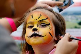 stock photo of lion  - Cute little girl with face painted like a lion - JPG