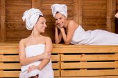 stock photo of sauna woman  - Two attractive women wrapped in towel relaxing in sauna - JPG