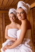 pic of sauna woman  - Two attractive women wrapped in towel sitting at sauna and smiling to you