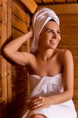 foto of sauna woman  - Beautiful young woman wrapped in towel relaxing in sauna and smiling to you - JPG