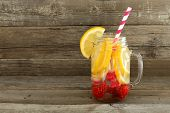 stock photo of masonic  - Detox water with lemon and raspberries in a mason jar with straw against a wood background - JPG