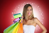 pic of starlet  - smiling woman with colorful bags on red background - JPG