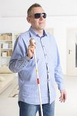 stock photo of blind man  - Blind man with white stick and dark glasses at home - JPG
