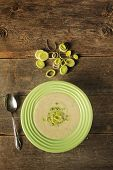 stock photo of leek  - Top view of a bowl of leek soup with fresh leek rings on a wooden background - JPG