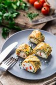 foto of curd  - Omelette rolls with curd and herbs on a plate - JPG