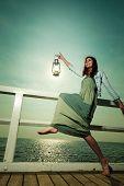 image of kerosene lamp  - Full length young woman on pier with oil kerosene lamp - JPG