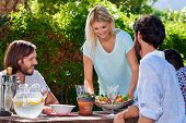 stock photo of gathering  - young woman serving salad to friends gathering at outdoor garden party - JPG