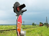 foto of railroad-sign  - Traffic lights and signs at the railroad crossing and the approaching train  - JPG