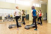 stock photo of step aerobics  - Group of women making step aerobics view from the backside - JPG