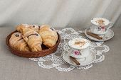 picture of doilies  - fresh breakfast with chocolate croissants on the woven basket and two cups of cappuccino coffee with cinnamon sticks on the table covered with grey linen cloth and decorated with white crochet doily - JPG