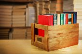 foto of wooden crate  - Books in wooden crate on bookshelves background - JPG
