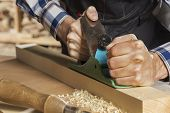 image of carpenter  - Close up of carpenter hands working with plane in his studio - JPG
