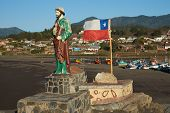 foto of promontory  - Colourfully painted statue of Saint Peter along side the flag of Chile on a rocky promontory sheltering the beach used by the fishing fleet in the small fishing village of Curanipe in the Maule Region of Chile - JPG