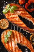 stock photo of grill  - Two grilled steak red fish salmon and vegetables on the grill - JPG
