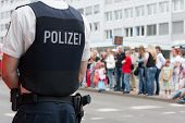 stock photo of vest  - German policeman with gun and bullet - JPG