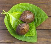 foto of green snake  - Snake Fruit and Green Leaf on the Wood Table - JPG