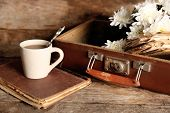 foto of old suitcase  - Old wooden suitcase with old books and flowers on wooden background - JPG