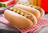 foto of hot dog  - Delicious barbecued hot dogs on a rustic picnic table. ** Note: Shallow depth of field - JPG