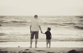 image of barefoot  - young happy father holding hand of little son walking together on the beach with barefoot in sand in front of sea waves the kid smiling and having fun with dad in Summer sunset coast - JPG