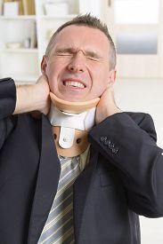 foto of neck brace  - Businessman at work wearing neck brace - JPG