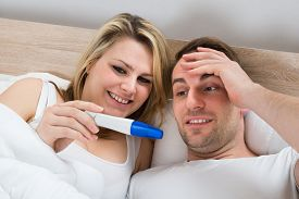 stock photo of pregnancy test  - Couple Looking At A Positive Pregnancy Test In Bedroom - JPG