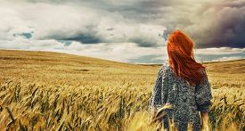 foto of red back  - fashion young red hair woman standing back outdoor on breathtaking view of dramatic storm sky in the field - JPG