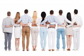 stock photo of bonding  - Full length rear view of group of diverse people bonding to each other while standing against white background - JPG