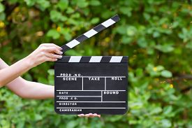 stock photo of clapper board  - Movie clapper board in female hands outdoors - JPG