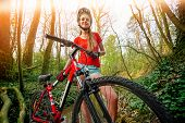 Bikes bicyclist girl. Girl wearing helmet and big backpack cycle bicycle into forest. Girl in cyclin poster