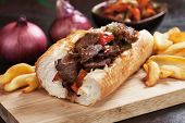 Philly steak sandwich with french fries served on wooden board poster