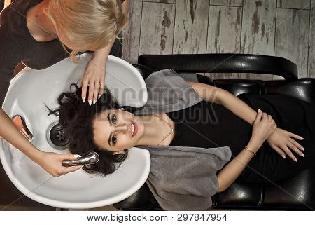 poster of Girls In The Beauty Salon. The Master Stylist Cleans The Hair Of The Client. Blonde Makes Brunette H