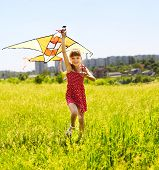 Child flying kite outdoor. little girl running across  green grass.