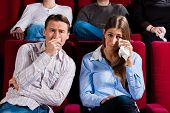 Couple and other people, probably friends, in cinema watching a movie; it seems to be a sad movie