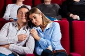 Couple and other people, probably friends, in cinema watching a movie; it seems to be a romantic movie
