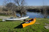 stock photo of upstream  - Two kayaks are near a river shore ready to make a trip upstream - JPG