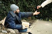 Woman Giving Alms To Poor Homeless Man On Street poster