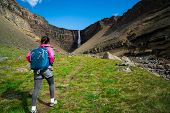 Traveler Hiking At Hengifoss Waterfall, Iceland. poster