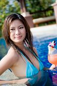 image of woman bikini  - A young attractive Asian woman holding a cocktail in swimming pool - JPG