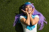 Smiling Asian Anime Girl In Purple Wig Lying On Green Grass poster