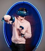 A Young Guy Plays Video Games In A Game Room In A Virtual Reality Helmet. Innovative Gaming Club. Hi poster