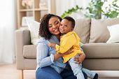 childhood, kids and people concept - happy african american mother with her baby son at home poster