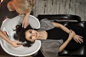 Girls In The Beauty Salon. The Master Stylist Cleans The Hair Of The Client. Blonde Makes Brunette H poster