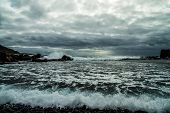 View From A Stony Shore To A Raging Ocean Wave During A Autumn Storm With A Horizon Line And Little  poster